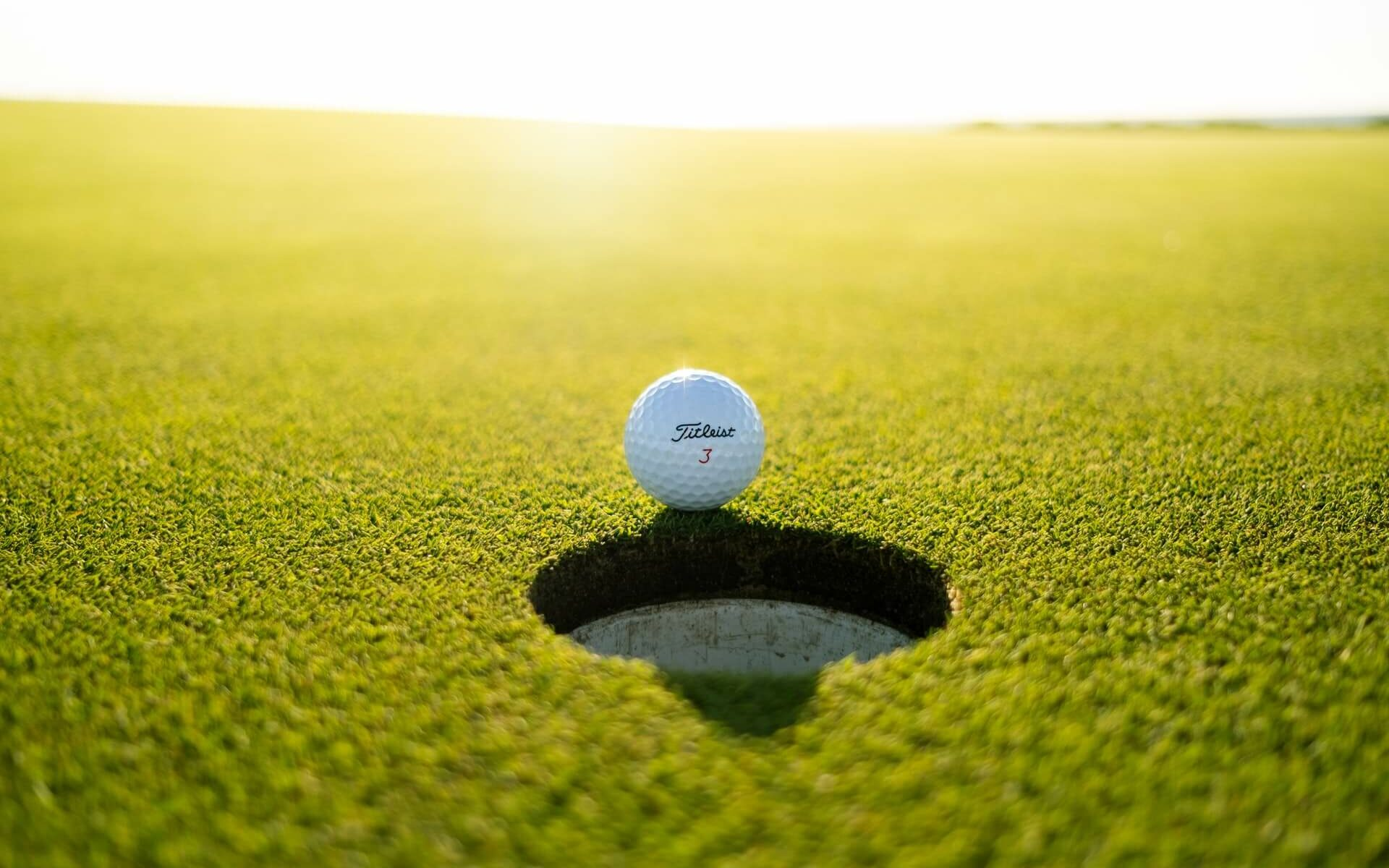 A Titleist 3 golf ball sitting at the very edge of the hole on a putting green in the Bahamas