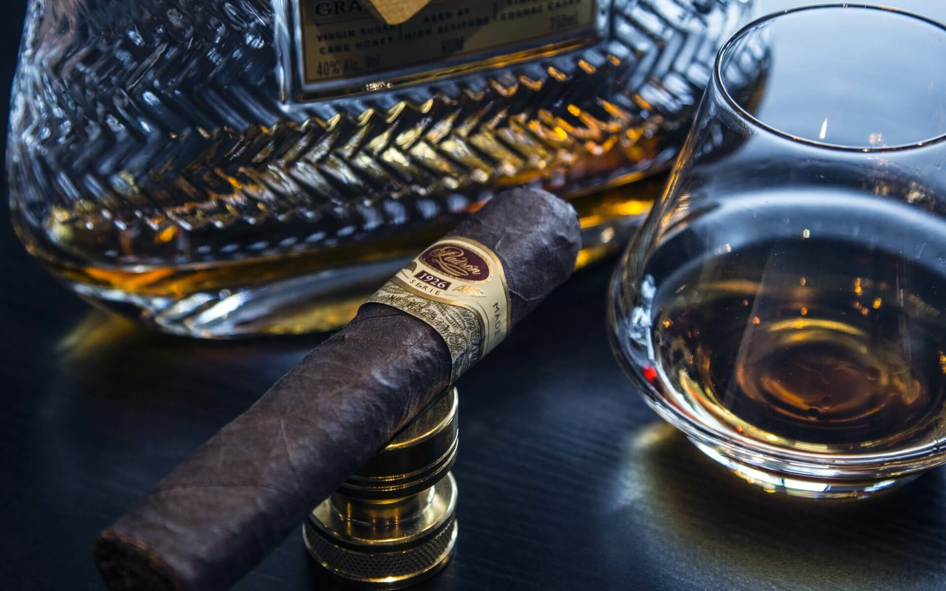 A hand rolled Bahamian cigar sits next to a glass of rum on a dark wooden table