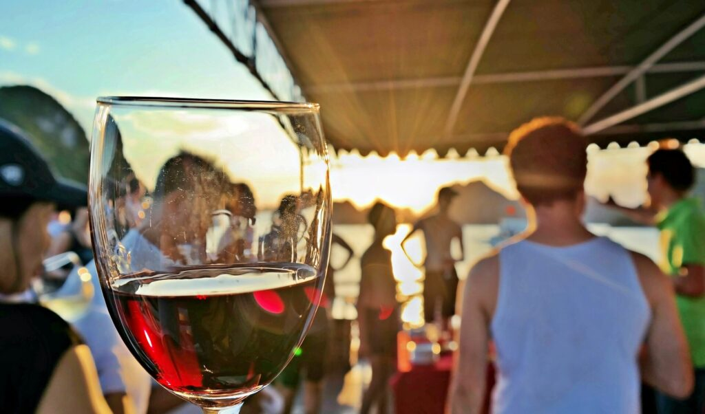 A glass of red wine held up in front of a crowd gathered on a sailboat during a boat christening ceremony