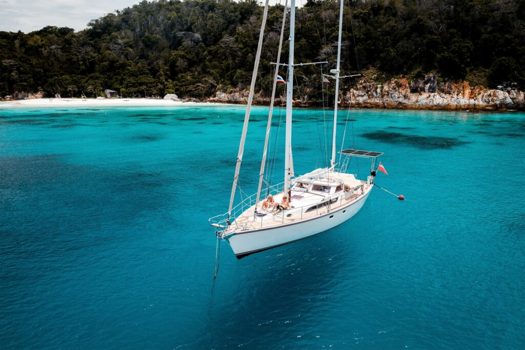 A sailboat anchored in crystal clear blue water off the shores of Thailand with marine solar panels mounted on the back of the boat