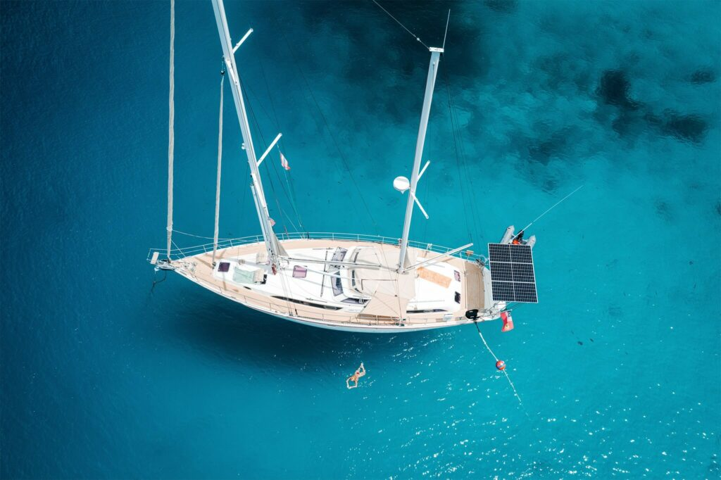 Aerial view of a sailboat with marine solar panels mounted at the stern