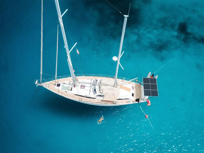 Aerial view of a sailboat with marine solar panels mounted on the stern of the boat