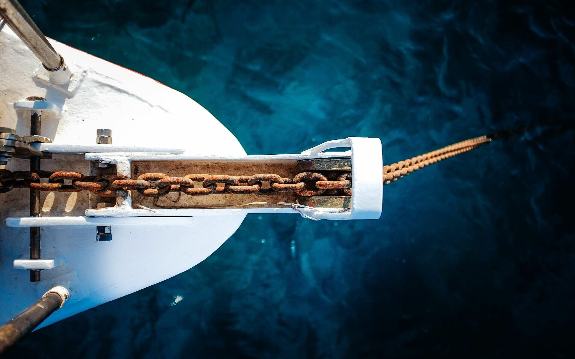 an anchor chain hangs off the bow of a white boat into cobalt blue waters