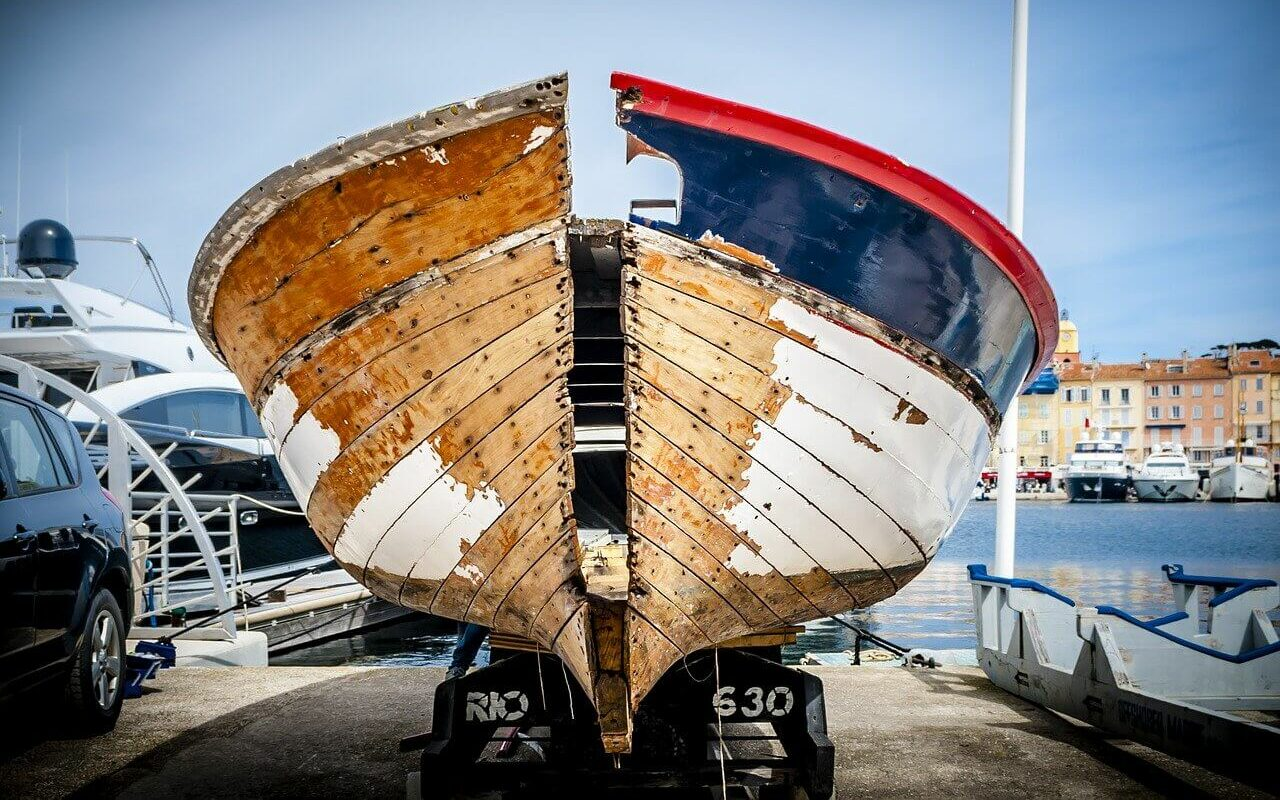 A boat sits on a trailer with deterioration showing on the exterior of the hull, showing how the cost of boat ownership includes boat depreciation
