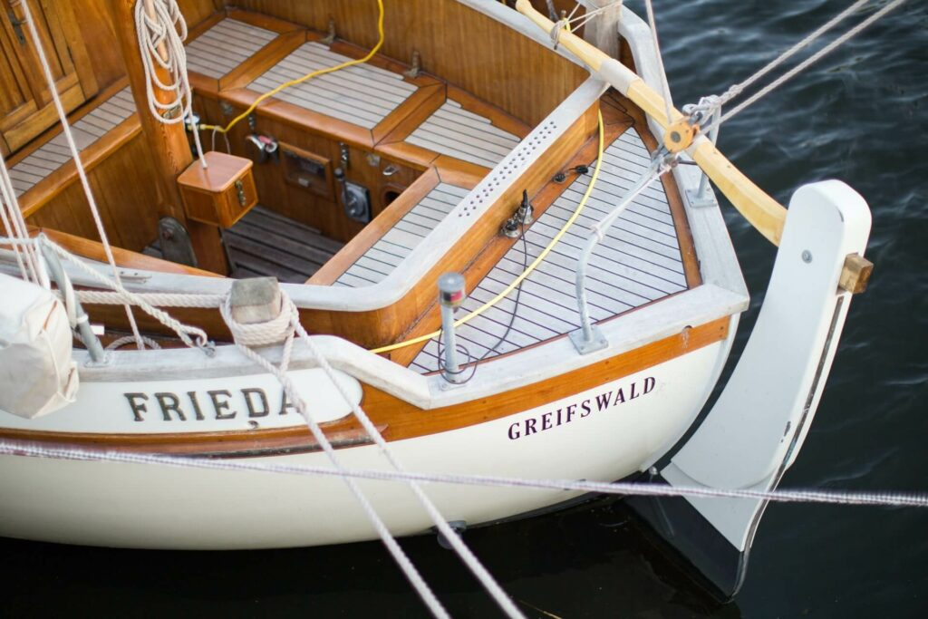 a white sailboat with brown wood trim that recently went through a boat restoration