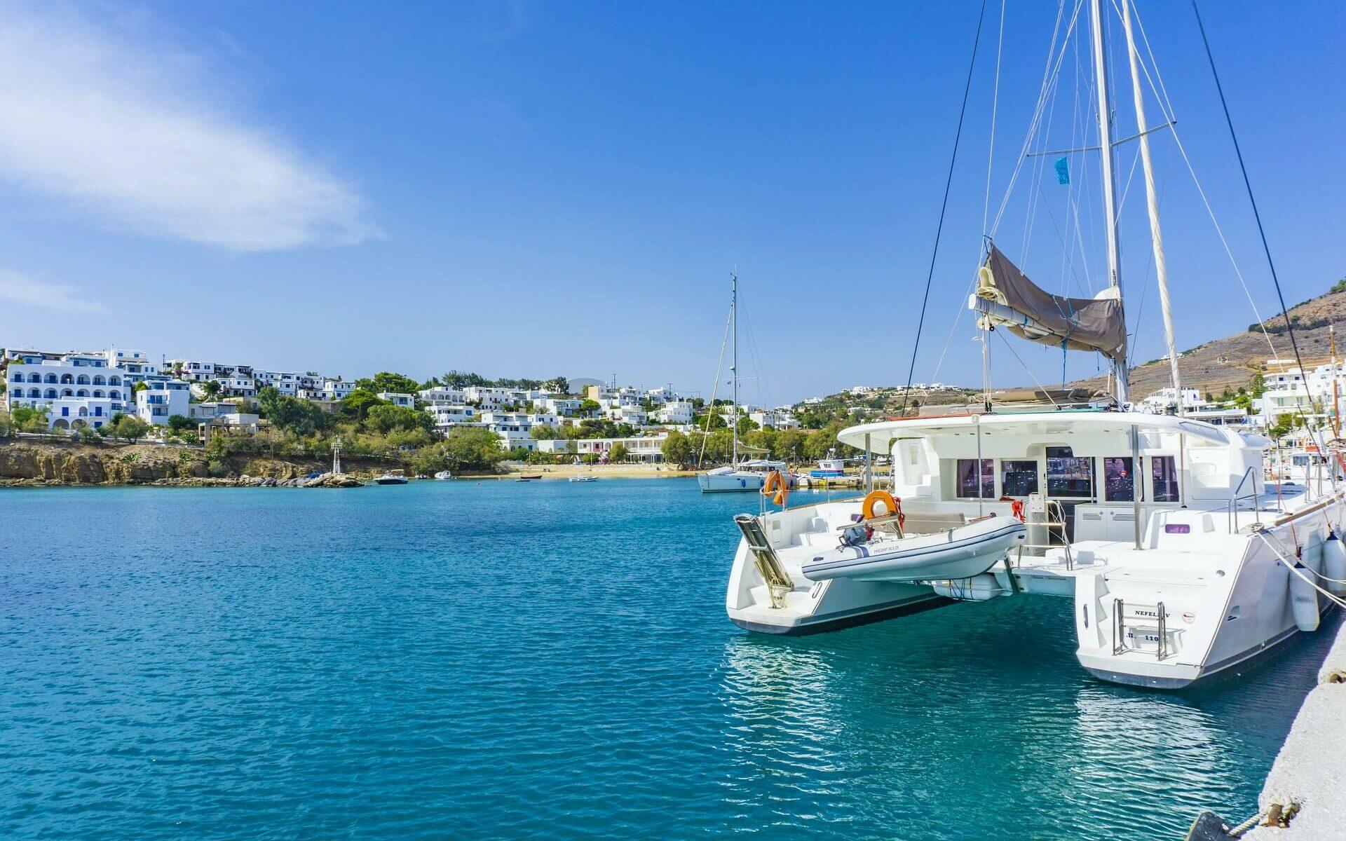 a white catamaran docked near shore in blue water