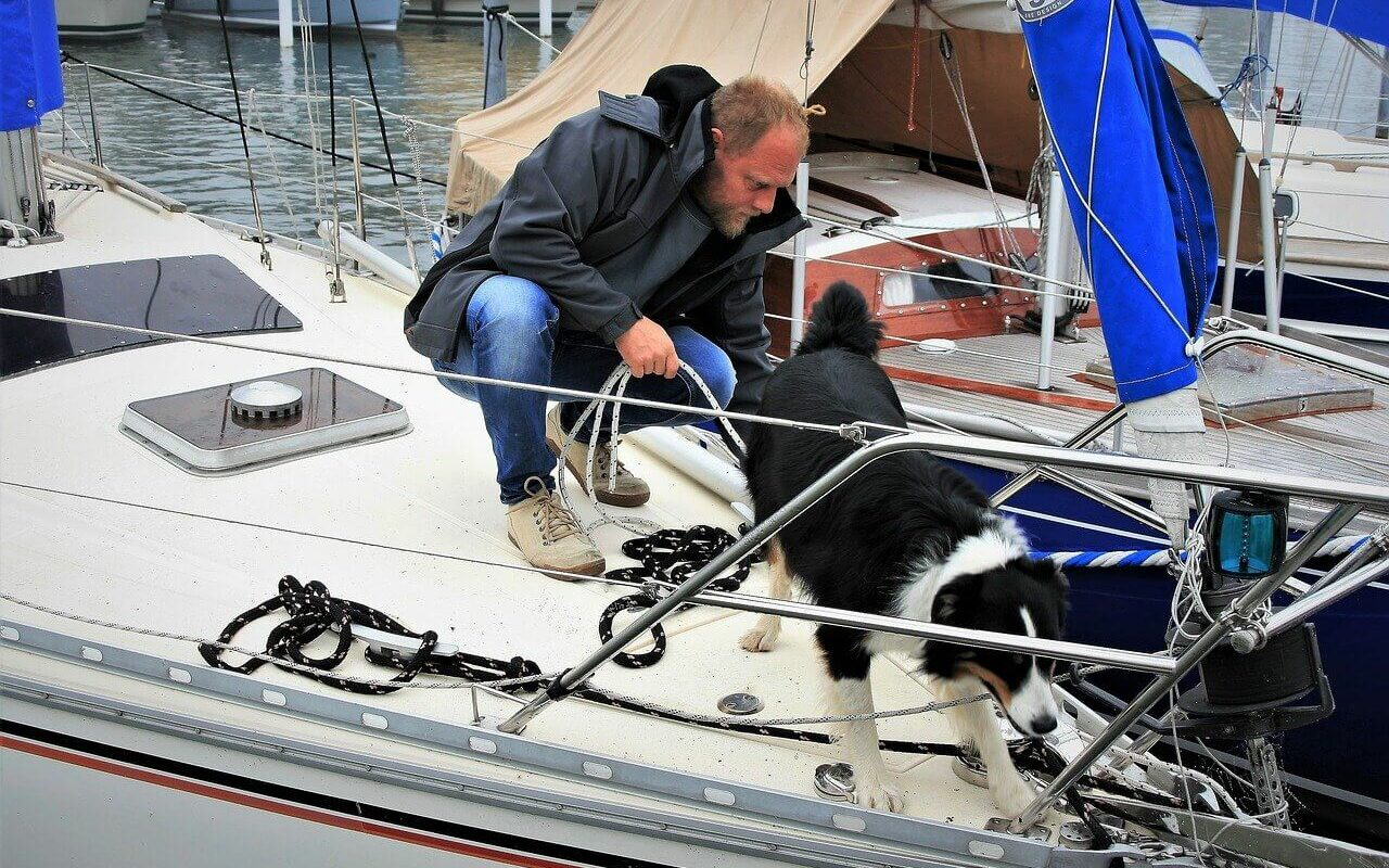 a man works next to his dog at the bow of his boat