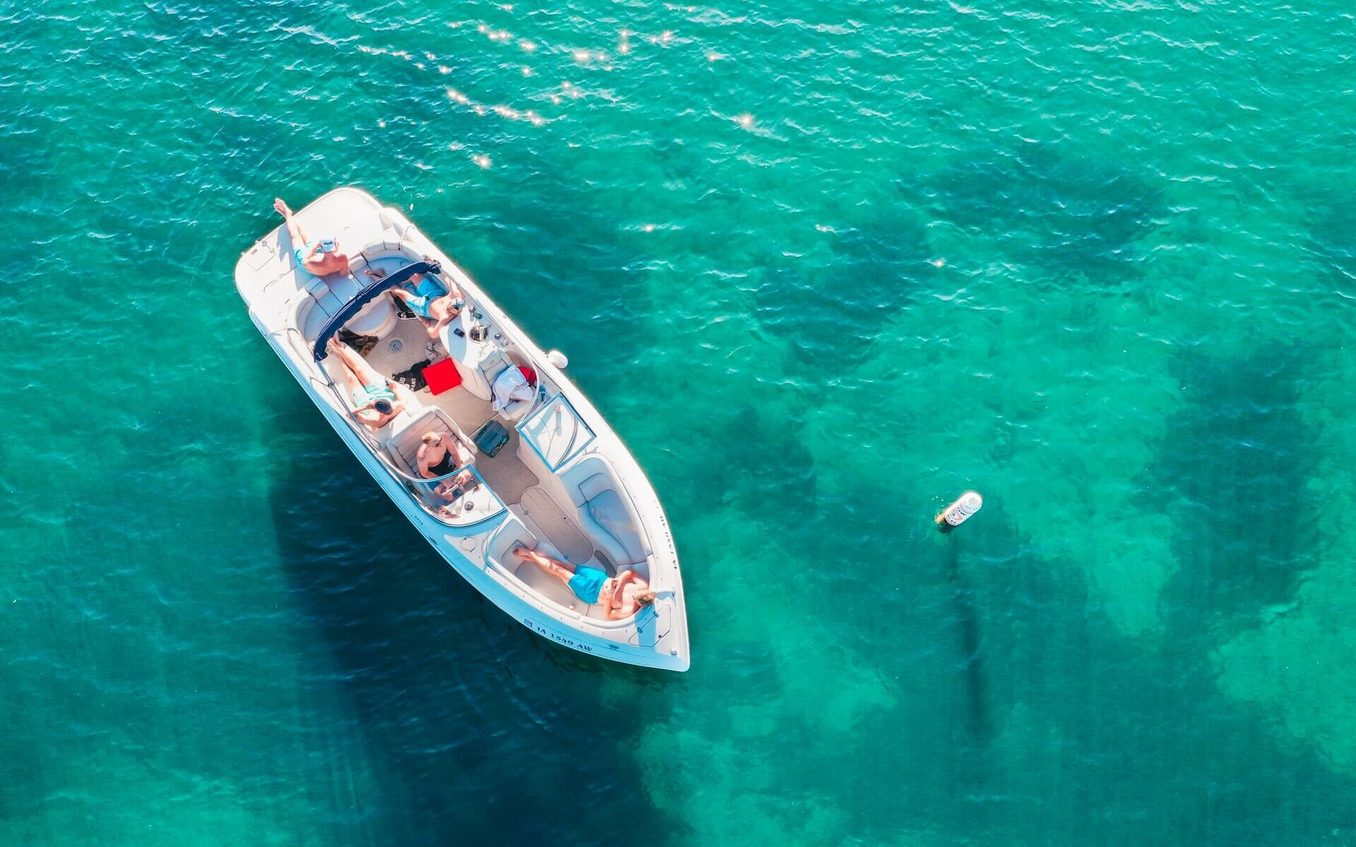 People lounging on a boat in the sun on clear, turquoise blue water