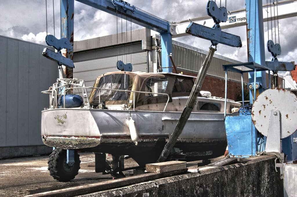 An old dirty boat on a trailer being prepared for boat restoration