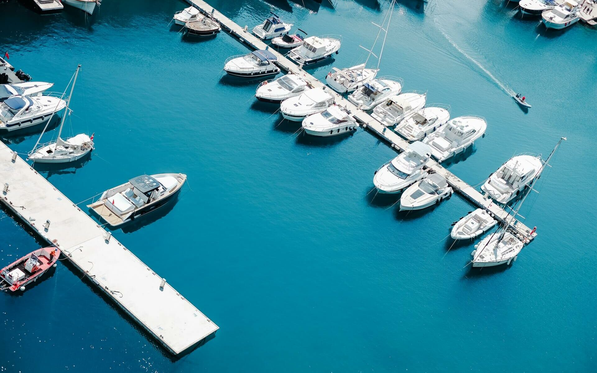 Various types of vessels at boat slips in a marina