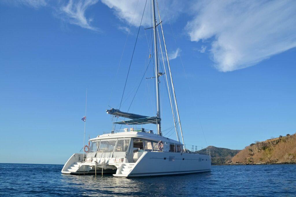 a white live aboard catamaran  anchored offshore