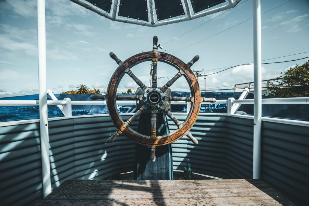an old wooden boat wheel ready for restoration on a sailboat
