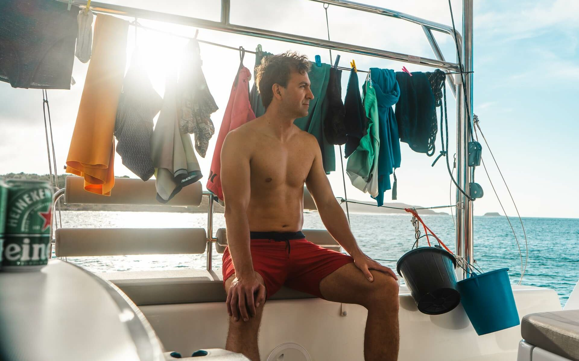 a man sits next to his hanging laundry while living on a boat