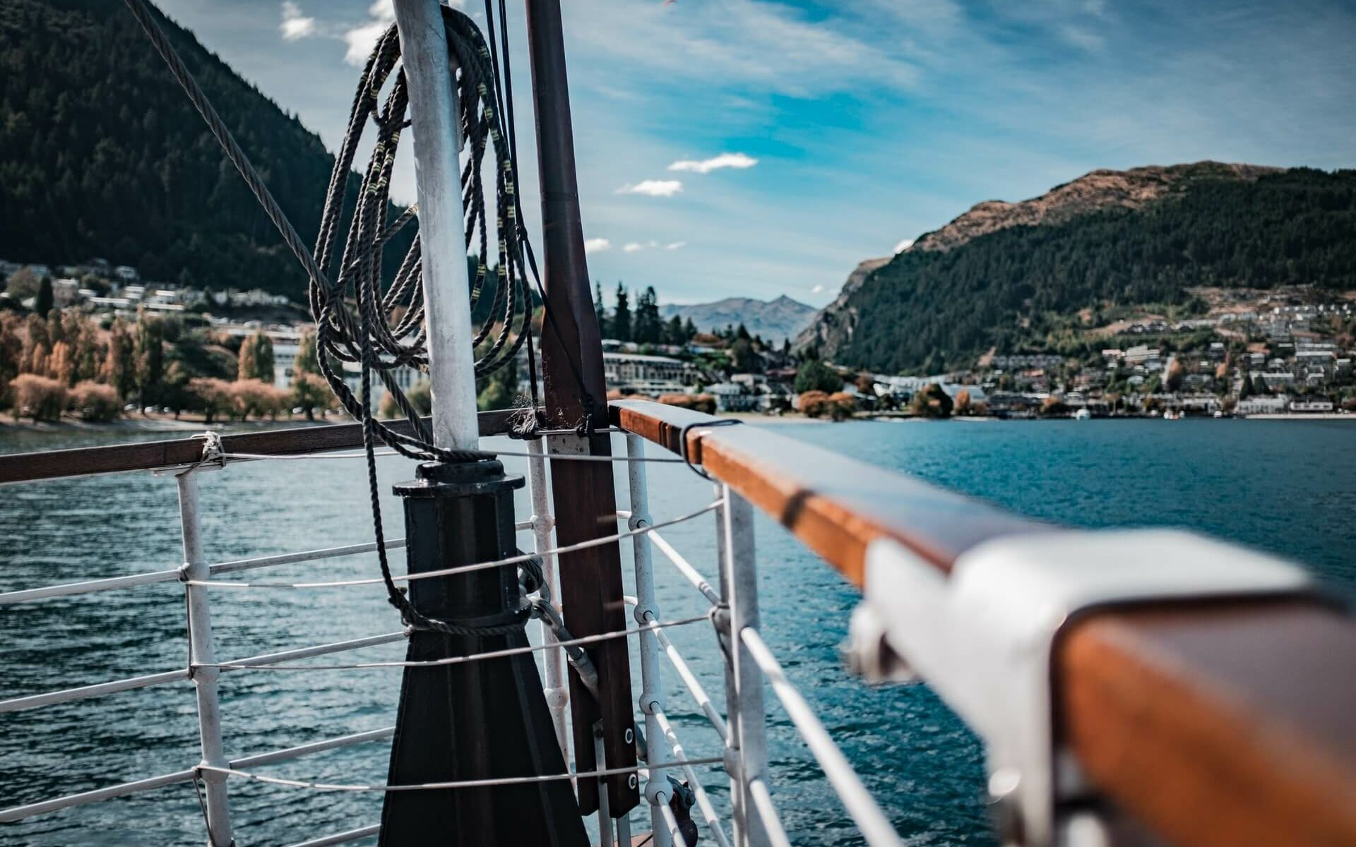Wooden railings on the bow of a boat looking toward land