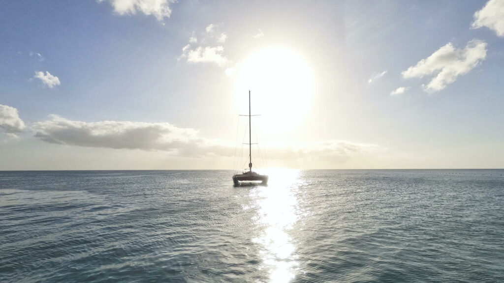 A catamaran in the ocean in front of a sunset
