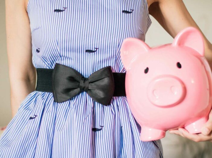 Woman in a blue whale dress holds a pink piggy bank