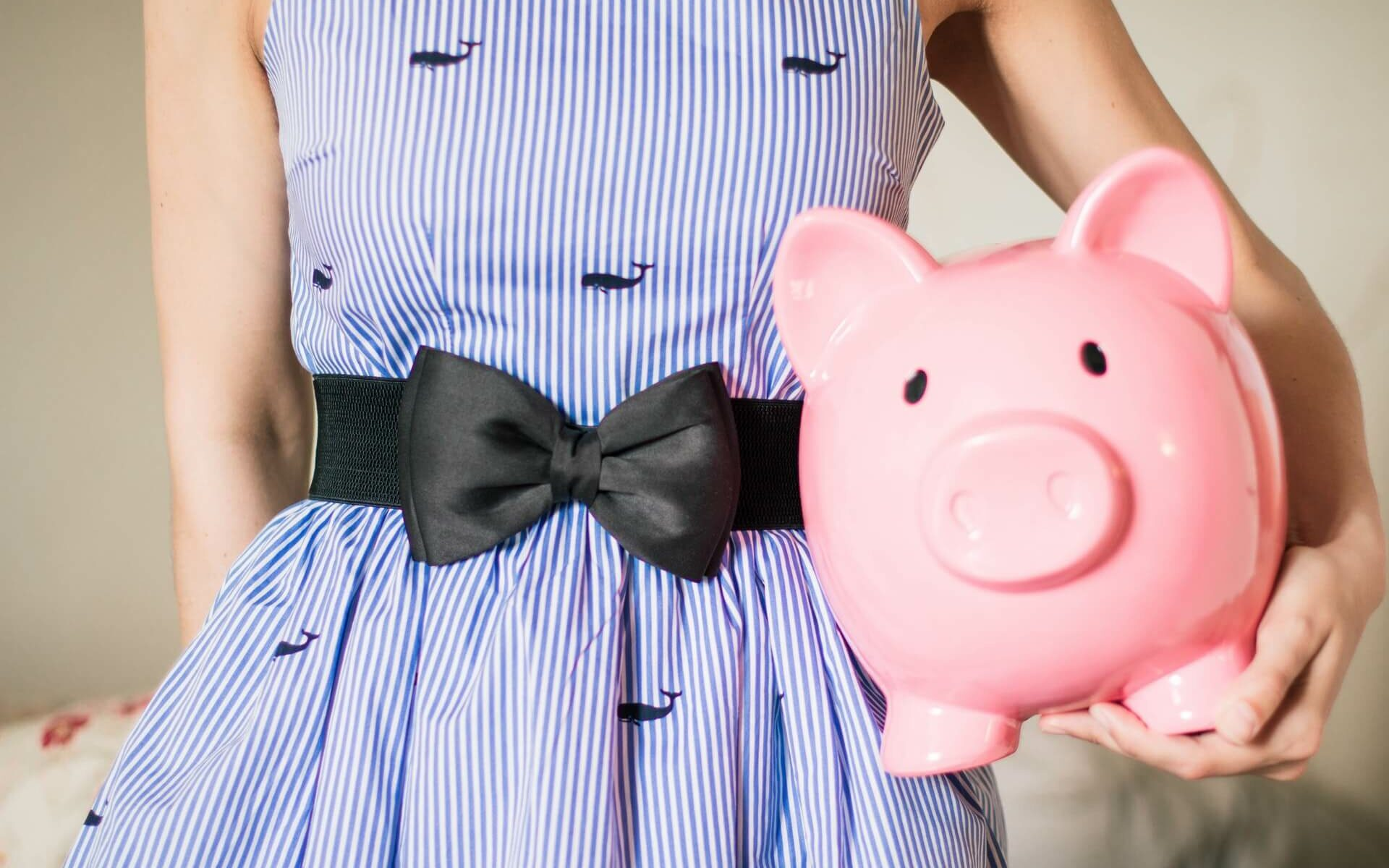 Woman in a blue whale dress holds a pink piggy bank to signify the cost of boat ownership