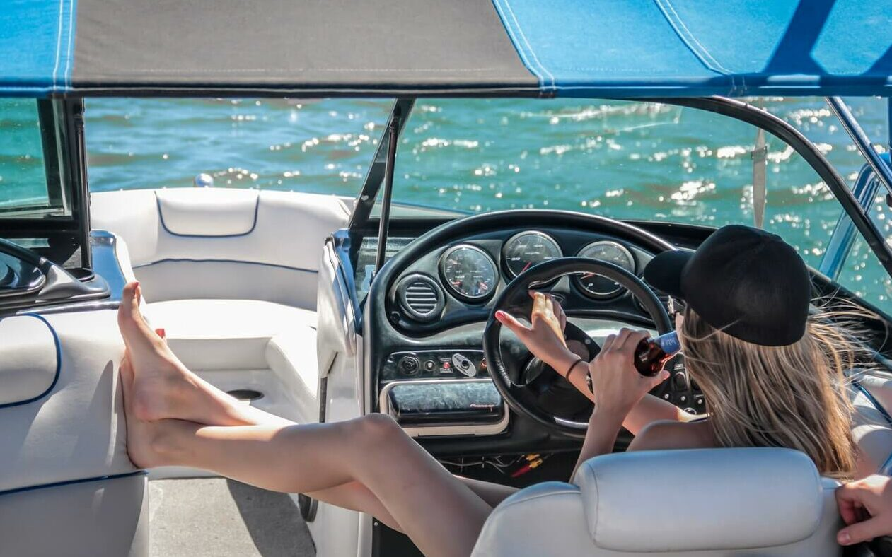 A woman in a hat sips a beer in the captains chair of a motorboat on a sunny day