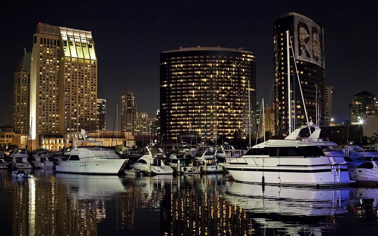 Several boats are parked at a marina at night in front of a city skyline