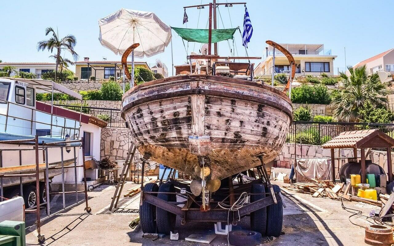 An old wooden boat on a trailer being prepared for maintenance and repairs, which is a big cost of boat ownership