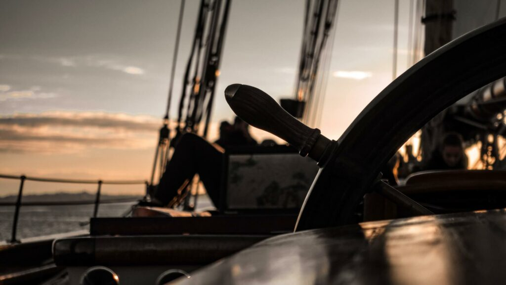 a wooden sailboat helm at dusk
