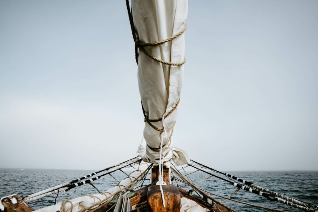 folded sails on a boat overlooking grey skies and the ocean