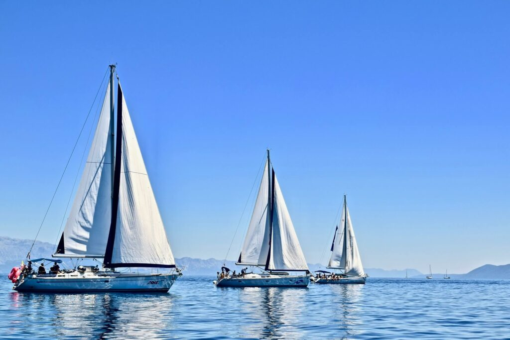 three boats anchored at sea during a tide transition period