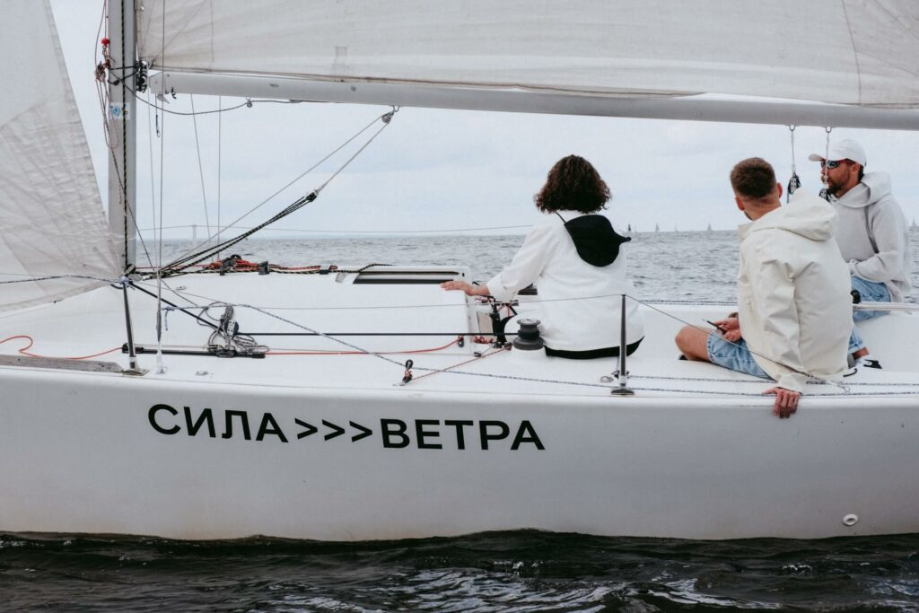 three people sitting on a white sailboat as it is driven by a self steering wind vane system