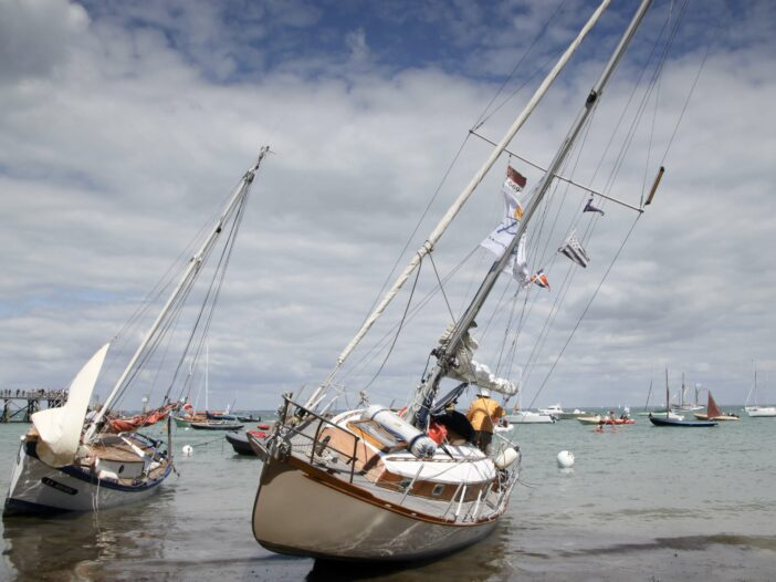 A sailboat is stranded on the sand at low tide near the shore