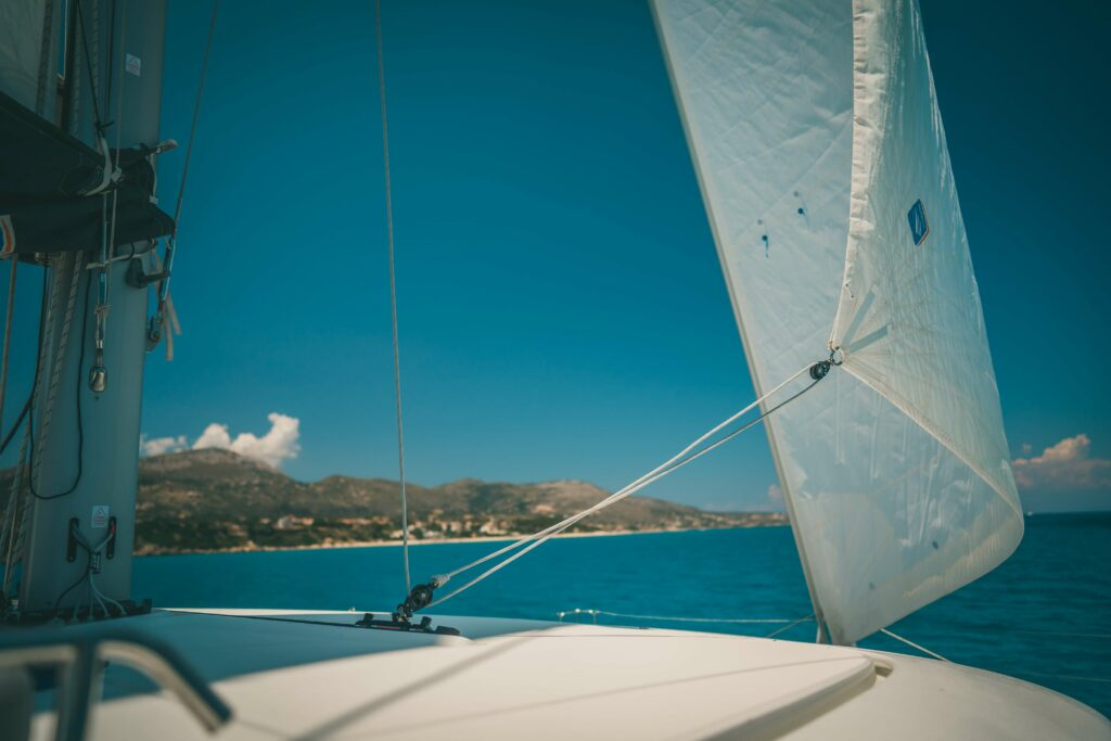 a boats sail blows in the wind on a sunny day