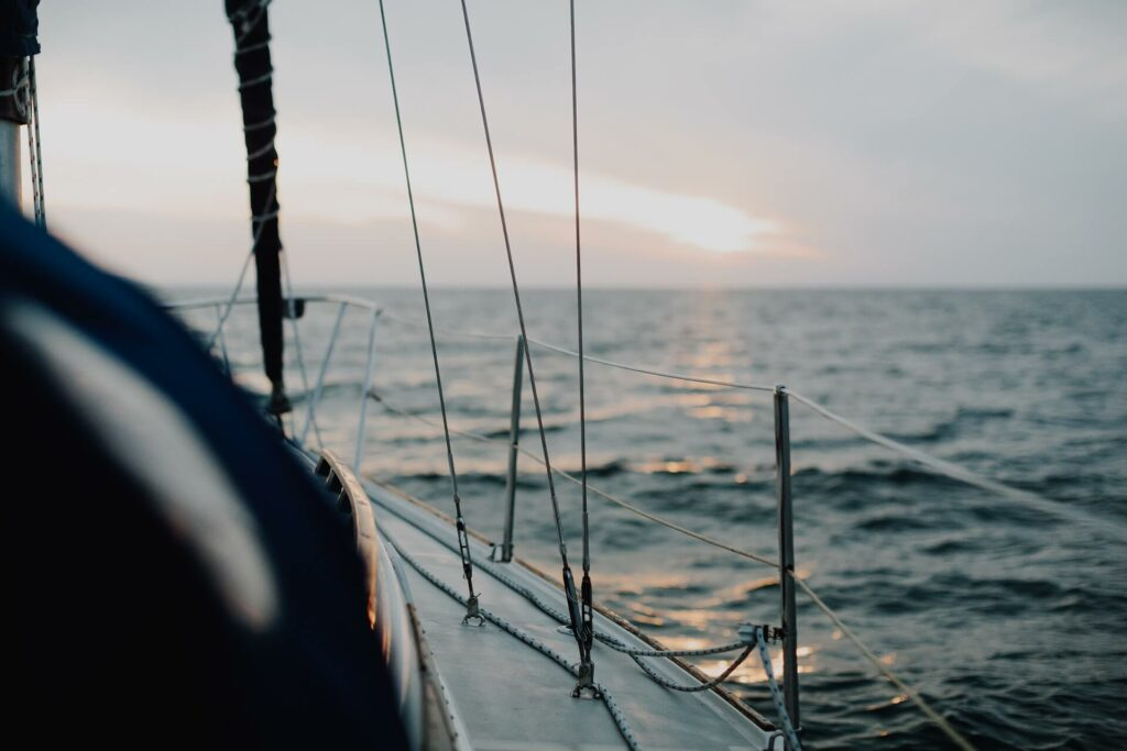 view of the ocean from the deck of a sailboat at dusk